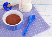 Baby food and milk on wooden table — Stock fotografie