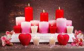 Belle candele con fiori sul tavolo su sfondo marrone — Foto Stock