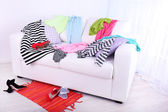 Messy colorful clothing on  sofa on light background — ストック写真