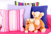 Two bears toy with pillows on sofa — Stock Photo