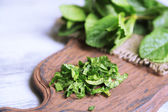 Mint on cutting board, on color wooden background — Stock Photo