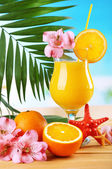 Refreshing orange cocktail on beach table — Stock Photo