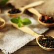 Assortment of dry tea in wooden spoons on table — 图库照片 #47922759
