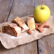 Tasty homemade apple strudel on paper napkin, on wooden background — Stock Photo #47923285