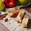 Tasty homemade apple strudel  on paper napkin, on wooden background — Stock Photo #47923307