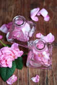 Rose oil in bottles on color wooden background — Stock Photo