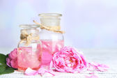 Rose oil in bottles on color wooden table, on light background — Stock Photo