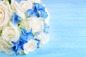 Beautiful wedding bouquet with roses on blue wooden table — Stock Photo