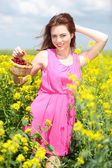 Beautiful young woman holding wicker basket with cherries in field — Stock Photo