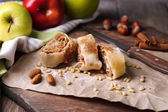 Tasty homemade apple strudel  on paper napkin, on wooden background — Stock Photo