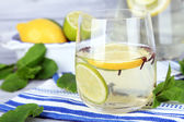 Fresh summer drink with lime and cloves in glass and jug, on color wooden background — Stock Photo