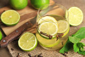 Fresh summer drink with lime and cloves in glass, on color wooden background — Stock Photo