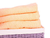 Color towels in wicket basket, isolated on white  — Stock Photo