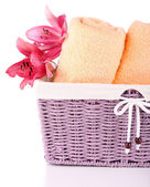 Color towels and lily flowers in wicket basket, isolated on white  — Stock Photo