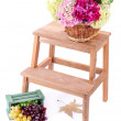 Wicker basket with flowers and fruits in wooden box,  on small wooden ladder, isolated on white — Stock Photo #47958459
