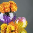 Beautiful flowers in vases with hydrogel on table on gray background — Stock Photo #47958881