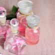 Rose oil in bottles on color wooden background — Stock Photo #47959237