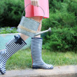 Young woman in rubber boots holding watering can, outdoors — Stock Photo #47959901