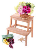 Wicker basket with flowers and fruits in wooden box,  on small wooden ladder, isolated on white — Stock Photo
