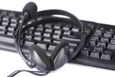 Headphone and keyboard, close-up, isolated on white — Stock Photo