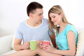 Loving couple sitting  with cups on sofa, on home interior background — Photo