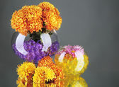Beautiful flowers in vases with hydrogel on table on gray background — Stock Photo