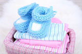 Baby clothes in basket on floor in room — ストック写真