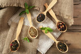 Assortment of dry tea in wooden spoons on table — Stock Photo