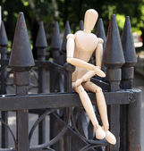 Wooden pose puppet on fence outdoors — Stock Photo