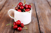 Ripe sweet cherries in cup on wooden table — 图库照片