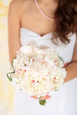 Bride holding wedding bouquet of white peonies, close-up, on light background — Stock Photo