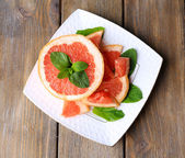 Ripe chopped grapefruit with mint leaves on plate, on wooden background — Stockfoto