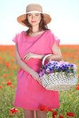 美しい若い女性にケシ畑で枝編み細工品バスケットを持って — ストック写真