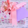 Pink gift with bow and flower on wooden table close-up — Stock Photo #47962755