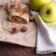 Tasty homemade apple strudel  on paper napkin, on wooden background — Stock Photo #47965717