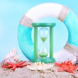 Hourglass in sand on blue sky background — Stock Photo #47967501