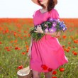 Beautiful young woman holding wicker bag in poppy field — Stock Photo