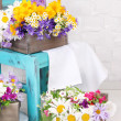 Beautiful flowers in crates on small chair on light background — Stock Photo #47968873