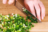 Female hand cutting chives on cutting board — Stock Photo