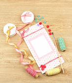 Beautiful hand made post card and scrapbooking elements, on wooden table — Stock Photo