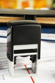Stamp with notepads and papers on table — Stock Photo