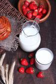 Reife süße erdbeeren in hölzerne schüssel und krug mit milch auf farbigem hintergrund holz — Stockfoto