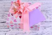 Dom-de-rosa com laço e flor em close-up de madeira mesa — Fotografia Stock