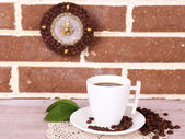 Still life cup of coffee and clock, on brick wall background — Stock Photo