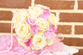 Beautiful wedding bouquet with roses on bricks wall background — Stock Photo