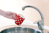 Hand holding  cup of water poured from  kitchen faucet — 图库照片