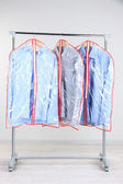 Office male clothes in cases for storing on hangers, on gray background — Stockfoto