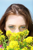 Beautiful young woman in flower field — Stock Photo