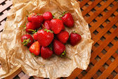Red ripe strawberries with chocolate on brown paper — Stock Photo