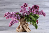 Beautiful lilac flowers in vase, on color wooden background — Stock Photo
